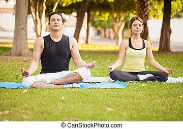 Una pareja joven haciendo yoga