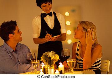 Una pareja joven ordena la cena