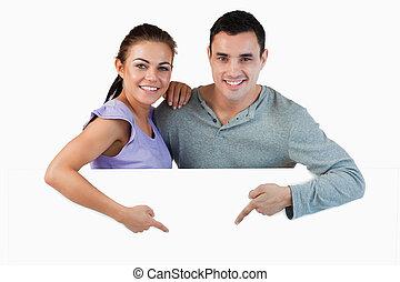Una pareja joven señalando el anuncio debajo de ellos