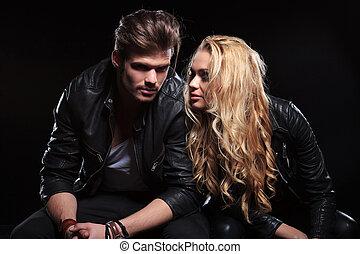 Una pareja joven sentada a su lado