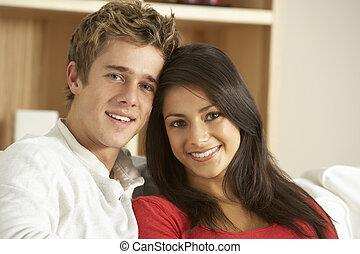 Una pareja joven sentada en el sofá