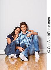 Una pareja joven sentada en el suelo