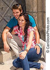 Una pareja joven sentada en los escalones del edificio sonriendo
