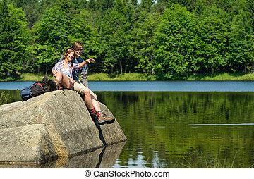 Una pareja joven sentada en roca junto al lago