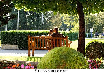 Una pareja joven sentada en un banco en el parque