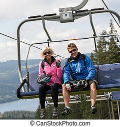 Una pareja joven sentada en una silla elevadora