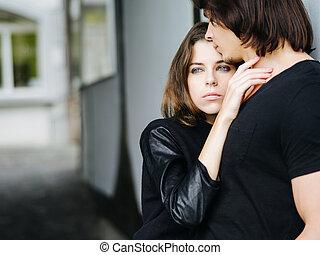 Una pareja joven sosteniéndose en la ciudad