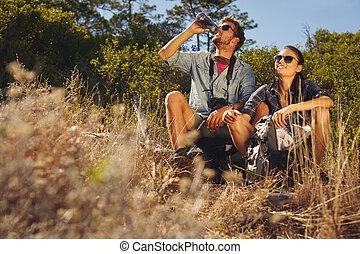 Una pareja joven tomando un descanso en la caminata