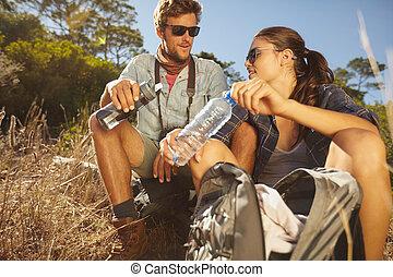 Una pareja joven tomando un descanso en una caminata