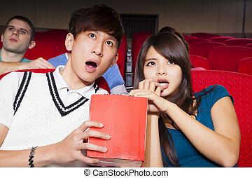 Una pareja joven viendo una película en el cine