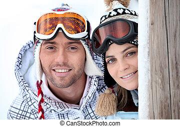 Una pareja joven y juguetona disfrutando sus vacaciones de esquí