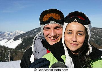 Una pareja joven y montañas nevadas en el fondo