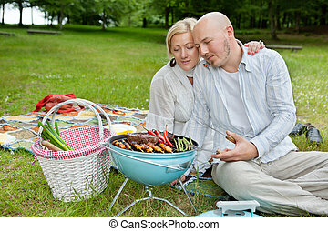 Una pareja madura cocinando en un picnic al aire libre