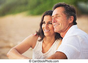 Una pareja madura disfrutando del atardecer en la playa
