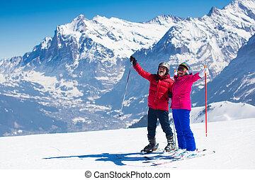 Una pareja madura esquiando en las montañas