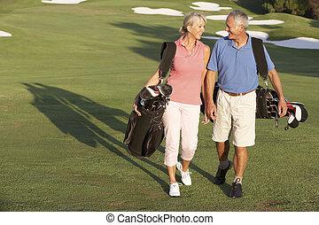 Una pareja mayor caminando por el campo de golf llevando bolsas