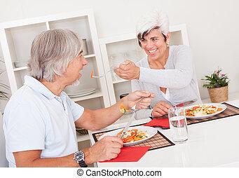 Una pareja mayor comiendo