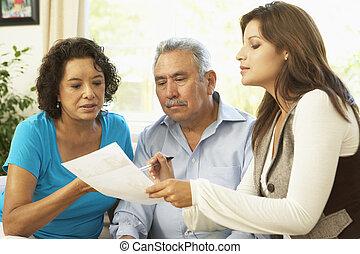Una pareja mayor con asesor financiero en casa