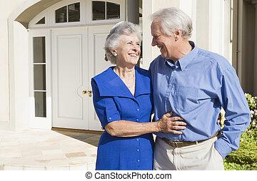 Una pareja mayor de pie fuera de casa