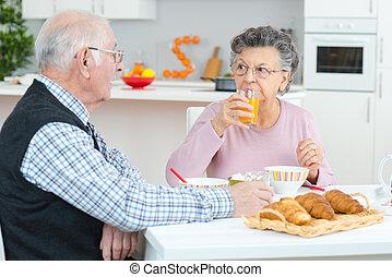 Una pareja mayor desayunando