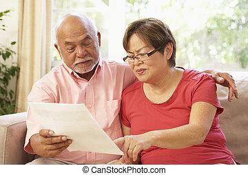 Una pareja mayor discutiendo sobre documentos en casa