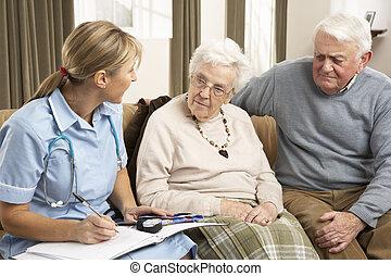 Una pareja mayor en discusión con un visitante de la salud en casa
