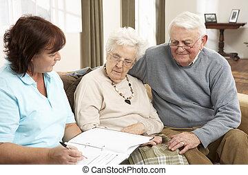 Una pareja mayor en discusión con un visitante en casa