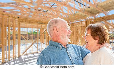 Una pareja mayor en el lugar dentro de su nueva estructura de construcción.
