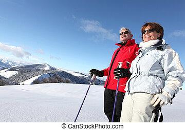Una pareja mayor esquiando