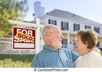 Una pareja mayor frente a una firma de bienes raíces vendidas, casa