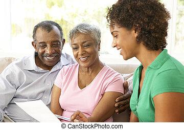 Una pareja mayor hablando con asesor financiero en casa