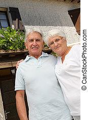 Una pareja mayor parada frente a una casa