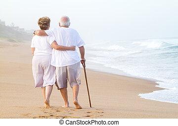 Una pareja mayor paseando por la playa