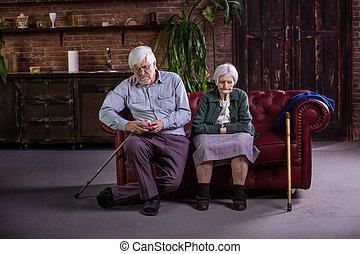 Una pareja mayor sentada en el sofá. Pareja en una pelea, sin hablar entre sí.