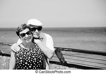Una pareja mayor sentada en la playa
