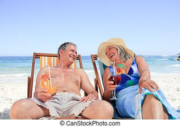 Una pareja mayor sentada en las sillas de cubierta