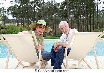 Una pareja mayor sentada en las sillitas junto a una piscina
