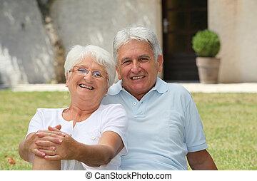 Una pareja mayor sentada frente a una casa