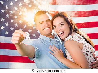 Una pareja militar con llaves de casa frente a la bandera americana