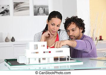 Una pareja mirando un modelo arquitecto de un nuevo desarrollo
