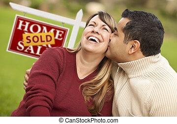 Una pareja mixta frente a un cartel de bienes raíces vendido