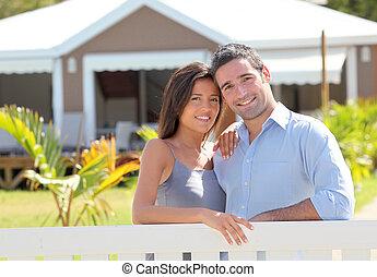 Una pareja parada frente a un nuevo hogar