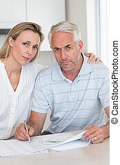 Una pareja preocupada trabajando en sus finanzas