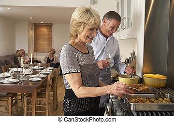 Una pareja preparando comida para una cena