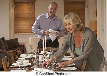 Una pareja preparando la mesa para una cena