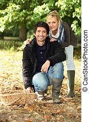 Una pareja que recoge hongos.