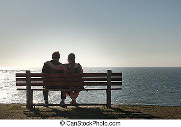 Una pareja que se relaja en un banco de vista del océano
