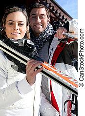 Una pareja que va a esquiar en un invierno soleado