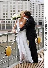 Una pareja recién casada besándose en la escena urbana