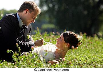 Una pareja recién casada roman en el campo